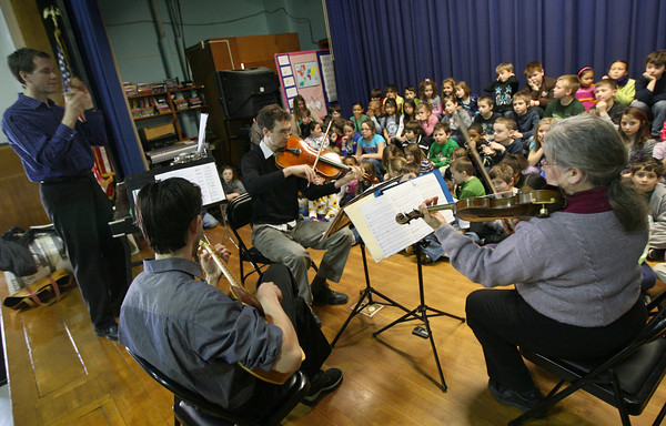Gloucester: Robert Schulz, Orlando Cela, Mark Berger, and Maria Benotti of the chamber group, Music at Eden's Edge, perform for students at East Gloucester Elementary School yesterday morning. The group, which has been performing in Gloucester Schools since 1990 as part of their community outreach, is celebrating their 30th anniversary this year. Photo by Kate Glass/Gloucester Daily Times
