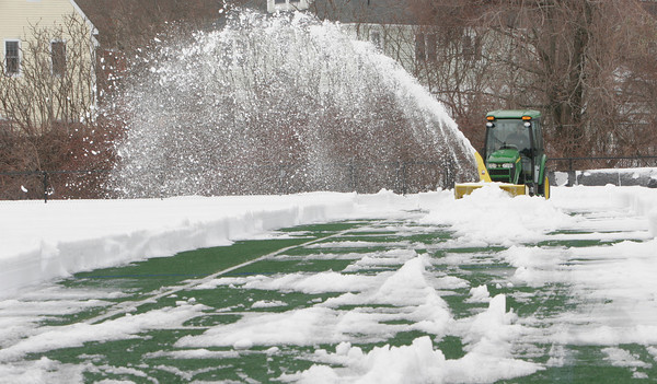 "Manchester: Joe Lucido removes snow from a section of Ed Field Field so athletes will have somewhere to practice when the spring sports season begins in two weeks. ""I'm trying to jump start mother nature,"" he said. Photo by Kate Glass/Gloucester Daily Times"