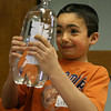 "Gloucester: Luke Sargent squeezes a 2-liter bottle to make a pen cap float up and down during a lesson on cartesian divers at ""March Madness: Science with Lisa"" at the Sawyer Free Library yesterday. Photo by Kate Glass/Gloucester Daily Times"