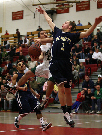 Salem: Manchester Essex guard Joe Burgess tries to shoot past St. Mary's guard Devin Thompson during the MIAA Division 4 North Semi-Finals at Salem High School last night. Photo by Kate Glass/Gloucester Daily Times