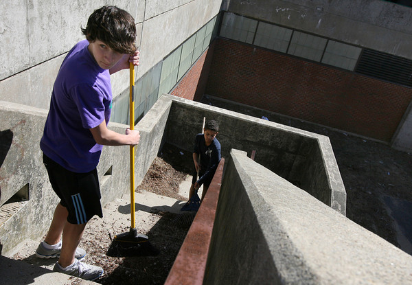 Gloucester: Cody Eaton and Noah Ashe sweep the steps behind O'Maley Middle School during a spring cleanup yesterday afternoon. The two students, who are on the track team, will receive a discount on their sports user fees for their work. Photo by Kate Glass/Gloucester Daily Times