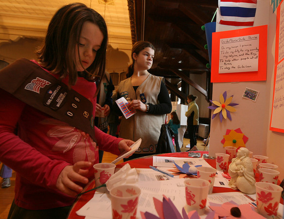 "Bonnie Gerhardt of Essex picks out a sample of Pad Thai candy after Emily Moore of Troop 523 explained the troop's presentation of Thailand during Girl Scouts of Cape Ann ""Thinking Day"" at Gloucester City Hall last week. Photo by Kate Glass/Gloucester Daily Times"