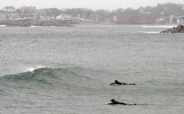 Rockport: Two surfers paddle out from Cape Hedge Beach in the snow in search of waves yesterday, which were diminishing quickly throughout the afternoon. Photo by Kate Glass/Gloucester Daily Times