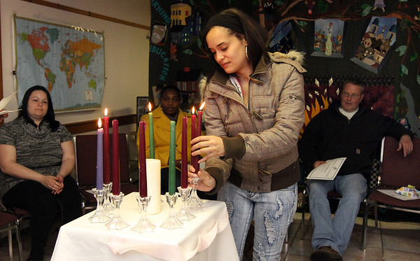 ALLEGRA BOVERMAN/Staff photo. Gloucester Daily Times. Gloucester: Elda Rodriguez, a graduate of the Wellspring House Adult Learning Initiative Program, lights a candle as she receives her certificate during the program's graduation ceremony on Wednesday evening.