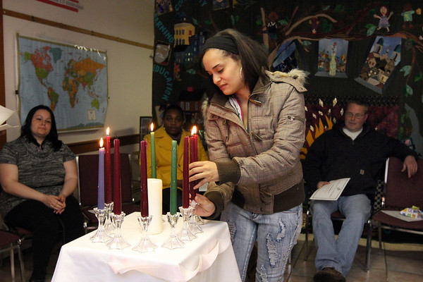 ALLEGRA BOVERMAN/Staff photo. Gloucester Daily Times. Gloucester: Elda Rodriguez, a graduate of the Adult Learning Initiative, lights a candle as she receives her certificate during the program's graduation ceremony on Wednesday evening.