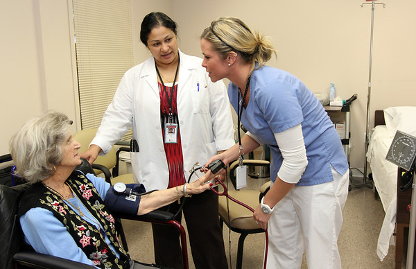 ALLEGRA BOVERMAN/Staff photo. Gloucester Daily Times. Gloucester: Dr. Roshni Samuel, center, looks on while personal care attendant Elizabeth Fitzgerald, right, takes the blood pressure of PACE participant Josie Testaverde on Friday afternoon. Samuel is a fulltime primary care physician at the center.
