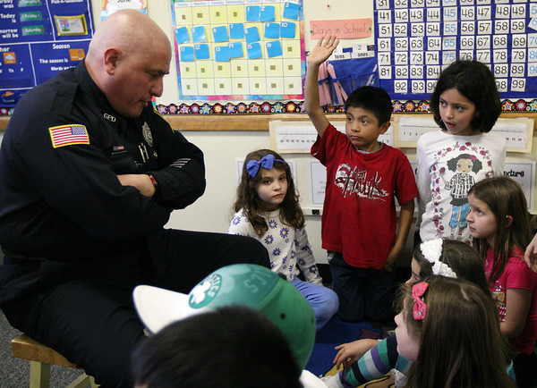 "ALLEGRA BOVERMAN/Staff photo. Gloucester Daily Times. Gloucester: <br /> Gloucester Police Officer Scott Duffany read ""Froggy Rides a Bike"" to second graders in Mary Hosman's class at Veterans Memorial Elementary School on Friday. About 13 ""local celebrities"" were on hand to read to every classroom in the school."