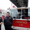 ALLEGRA BOVERMAN/Staff photo. Gloucester Daily Times. Gloucester: Gloucester Firefighters Jim Capillo, left, and Bob Rivas with Lawrence Ladder 4, right, a ladder truck lent to Gloucester by the Lawrence Fire Department. Gloucester's Ladder 1 is at far left. They are at the West Gloucester Fire Station.