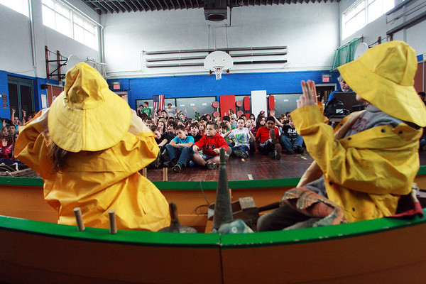Fourth-grader Cyrus Baumgaertel, left, and third-grader Morgan McGuire wear fishermen's clothing and sit in a dory in front of the third, fourth and fifth graders of West Parish School as Schooner Adventure sponsors an education outreach program about the history of Gloucester. Jesse Poole/Gloucester Daily Times March 16, 2012