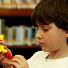 "ALLEGRA BOVERMAN/Staff photo. Gloucester Daily Times. Manchester: Danny Wood, 7, of Manchester works on building a model double helix out of Lego pieces during a Lego DNA workshop at Manchester Public Library on Thursday afternoon. The activity ties in with the medically themed activities at the library all through March that are connected with the Manchester Reads 2012 program centered on ""The Immortal Life of Henrietta Lacks"" by Rebecca Skloot."
