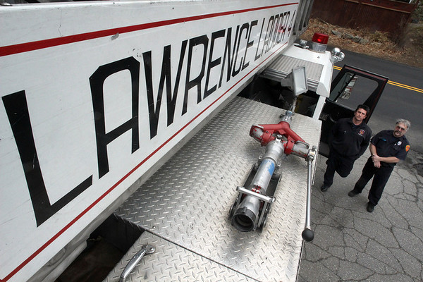 ALLEGRA BOVERMAN/Staff photo. Gloucester Daily Times. Gloucester: Gloucester Firefighters Bob Rivas and Jim Capillo with Lawrence Ladder 4, a ladder truck lent to Gloucester from Lawrence, at the West Gloucester Fire House on Concord St.