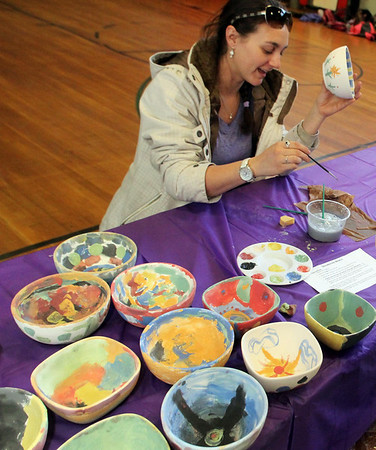 "ALLEGRA BOVERMAN/Staff photo. Gloucester Daily Times. Gloucester: Plum Cove Elementary School after school program coordinator Patrice Palmisano paints a bowl during the school's after school program on Tuesday afternoon. About 30 bowls were painted there by students and the program coordinators for The Open Door Empty Bowl Dinner that will take place on Thurs. May 10 from 4-8 p.m. at Cruiseport Gloucester. See the website for more information: <a href=""http://www.foodpantry.org"">http://www.foodpantry.org</a> ."