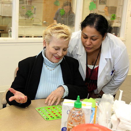 ALLEGRA BOVERMAN/Staff photo. Gloucester Daily Times. Gloucester: Dr. Roshni Samuel, right, now a fulltime primary care physician at PACE, looks at the BINGO board that Bonnie Sweet is playing on Friday at the Emerson Avenue center.
