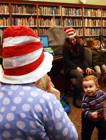 """Mario Zanetti, 18 months, of Manchester, excitedly stumbles toward Sara Collins, children's librarian at Manchester Public Library, as she reads """"Happy Birthday To You"""" by Dr. Suess in celebration of the author's birthday on Friday morning. Jesse Poole/Gloucester Daily Times March 2, 2012"""