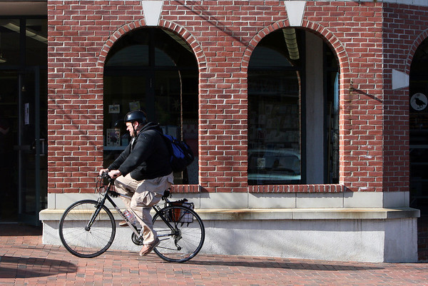ALLEGRA BOVERMAN/Staff photo. Gloucester Daily Times. Gloucester: It was mild, sunny and breezy on Thursday in Cape Ann. A man bicycles through downtown Gloucester along Main Street.