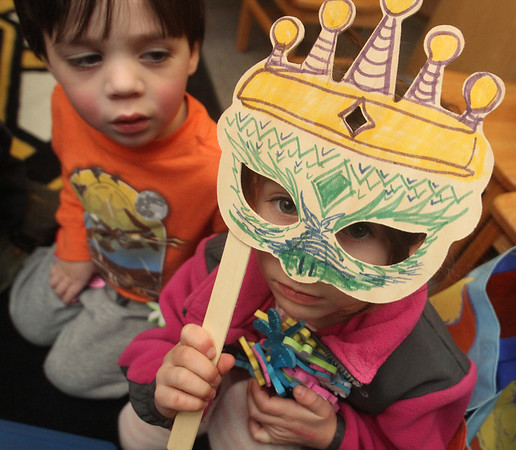 """ALLEGRA BOVERMAN/Staff photo. Gloucester Daily Times. Manchester: Children learned about the festive Jewish holiday of Purim on Tuesday at Manchester Public Library. They heard the telling of The Story of Esther and Sammy Spider's First Purim. The participants used noisemakers every time the name of the bad guy in The Story of Esther, Haman, was mentioned, and when Queen Esther's name was spoken, all would say """"Ohh, lala!"""" and when her uncle Mordechai's name was mentioned, they would say """"Hip Hip Hooray!"""" The Robert I Lappin Charitable Foundation of Salem sponsored the free program at the library. Children also ate hamentashen, which are triangle-shaped cookies filled with preserves, and made little baskets to bring treats to neighbors and friends for the holiday, which starts Purim begins in the evening of Wednesday, March 7, 2012, and ends in the evening of Thursday, March 8, 2012. Sylvia McCavanagh, 5, of Manchester, holds a mask to her face while gathering foam decorating stickers for her gift basket as Noah Cohen, 2, of Manchester, left, looks on."""
