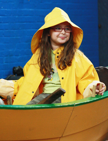 Third-grader Morgan McGuire wears fishermen's clothing and sits in a dory in front of the third, fourth and fifth graders of West Parish School as Schooner Adventure sponsors an educational outreach program about the history of Gloucester. Jesse Poole/Gloucester Daily Times March 16, 2012
