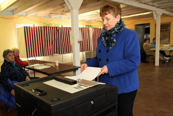 ALLEGRA BOVERMAN/Staff photo. Gloucester Daily Times. Gloucester: Judie Gorton, right, casts her vote at the Lanesville Community Center on Super Tuesday. Looking on, from far left are poll workers Judy Juncker and Carolyn Benga.