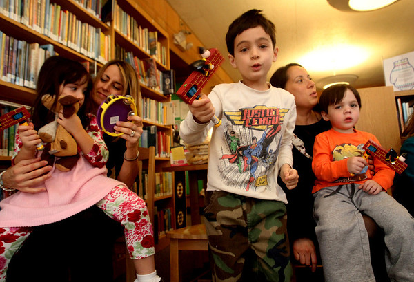 """ALLEGRA BOVERMAN/Staff photo. Gloucester Daily Times. Manchester: Listening to """"The Story of Esther,"""" at the Manchester Public Library on Tuesday are, from left: Skyler Hough, 5, and her mother Jennifer Ware-Hough, both of Essex, Josh Cohen, 5, his mom Jenai Cohen and brother Noah, 2, of Manchester.  The participants used noisemakers every time the name of the story's bad guy, Haman, was mentioned, and when Queen Esther's name was spoken, all would say """"Ohh, lala!"""" and when her uncle Mordechai's name was mentioned, they would say """"Hip Hip Hooray!"""" The Robert I Lappin Charitable Foundation of Salem sponsored the free program at the library. Children also had hamentashen, which are triangle-shaped cookies filled with preserves, and made little baskets to bring treats to neighbors and friends for the holiday, which starts Purim begins in the evening of Wednesday, March7, 2012, and ends in the evening of Thursday, March8, 2012."""