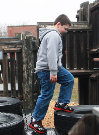 ESSEX—First-grader Josh Heath maneuvers on the playground tires after school at Essex Elementary School on Wednesday. Jesse Poole/Gloucester Daily Times March 14, 2012
