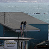 ALLEGRA BOVERMAN/Staff photo. Gloucester Daily Times. Gloucester: Men workong atop a roof near the waterfront in Gloucester on Thursday afternoon.