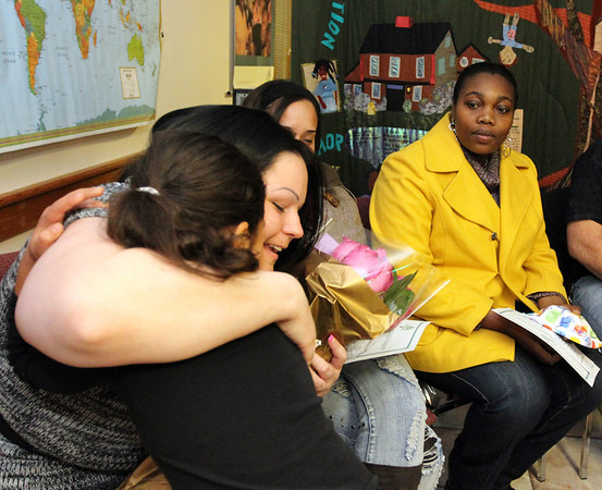 ALLEGRA BOVERMAN/Staff photo. Gloucester Daily Times. Gloucester: Alicia Silas is given a bouquet of roses and is hugged by Trinity O'Leary, 7, child of one of Silas' friends, after the Wellspring House Adult Learning Initiative graduation ceremony on Wednesday evening. Seated next to Silas from left are fellow graduates Elda Rodriguez and Tasha Walker.