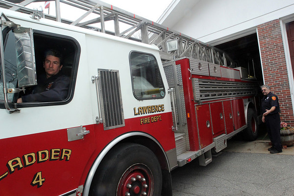 ALLEGRA BOVERMAN/Staff photo. Gloucester Daily Times. Gloucester: Gloucester Firefighters Bob Rivas (inside engine) and Jim Capillo with Lawrence Ladder 4, a ladder truck being lent to them by the Lawrence Fire Department, at the West Gloucester Fire Station.