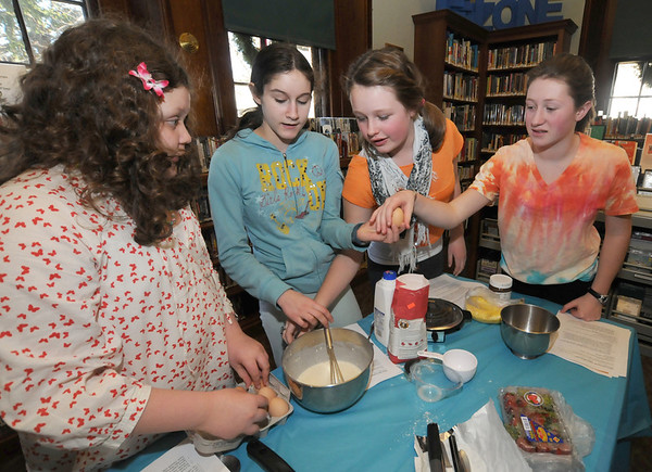 Manchester:Sasa Williams, 10, Nellie Boling, 13, Amber Shaw, 12,and Anna Arnsten, 12, make a crepe batter as part of  Teen Healthy Cooking Class with Anna Tourkakis,held at the Manchester Library Wednesday. The event featured 14 kids making 3 recipes with the help of Tourkakis along with the chocolate and fruit filled crepes the fare included Panzanella, an Italian bread salad, and . Asian chicken wraps. JIm Vaiknoras/staff photo