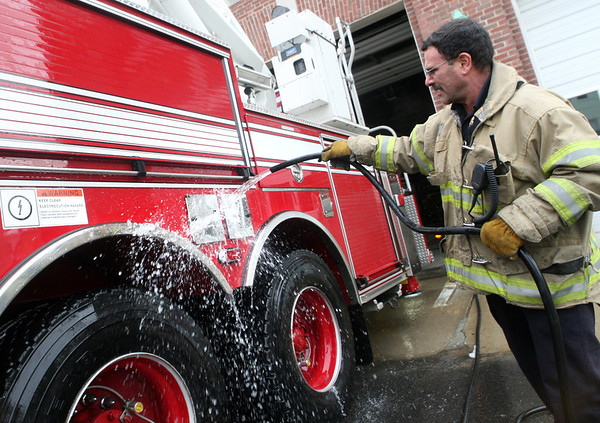 ALLEGRA BOVERMAN/Staff photo. Gloucester Daily Times. Gloucester: Gloucester Firefighter Glen Asaro washes Ladder 1 on Friday afternoon at the station. Firefighters take great pride in their vehicles and like having clean machines, he said. He's been a firefighter for 28 years.