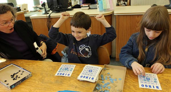 ALLEGRA BOVERMAN/Staff photo. Gloucester Daily Times. Essex: Participating in the Family Game Day at TOHP Burnham Public Library on Friday afternoon are members of the Adams family playing Bingo. From left are Carla Adams, Kevin Adams, 6, and Heather Adams, 8. Games people could play included Pictureka!, checkers, Guess Who?, Tumbling Towers, Backgammon, Scrabble and more.
