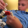 "ALLEGRA BOVERMAN/Staff photo. Gloucester Daily Times. Manchester: Patrick Cronin, 7, of Manchester works on building a model double helix out of Lego pieces during a Lego DNA workshop at Manchester Public Library on Thursday afternoon. The activity ties in with the medically themed activities at the library all through March that are connected with the Manchester Reads 2012 program centered on ""The Immortal Life of Henrietta Lacks"" by Rebecca Skloot"