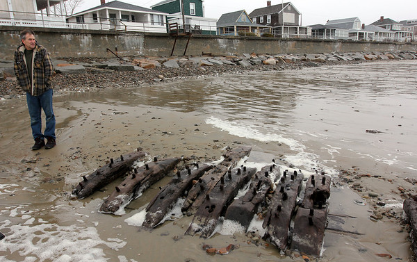 Allegra Boverman/Gloucester Daily Times. Ron Muise of Gloucester was looking at the now exposed shipwreck remains at Long Beach on the Rockport side on Thursday at low tide. The ship, which was The Surprise, of Wiscasset, Maine, is now visible due to a lot of erosion at the beach recently.