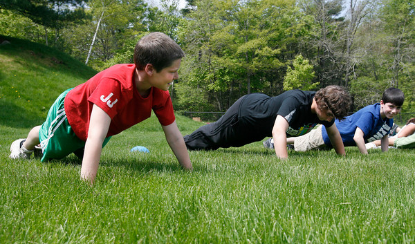Manchester: Ian Kennedy, Mike Falzarano, and Drew Aiello, all seventh grade students at O'Maley, see how many pushups they can do during the fitness portion of the Manchester Athletic Club's Enrichment Program. Photo by Kate Glass/Gloucester Daily Times