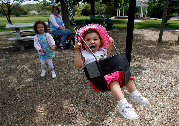 """Manchester: Gracie Gustafson, 3, pushes her sister, Jordan, 1, on the swings at Masconomo Park yesterday afternoon. Gracie said Jordan was sticking her tongue out to """"taste the wind."""" """"It tastes like butterscotch. I remember from when I used to stick my tongue out when I was a baby,"""" she said. Photo by Kate Glass/Gloucester Daily Times Wednesday, May 20, 2009"""