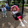 "Manchester: Gracie Gustafson, 3, pushes her sister, Jordan, 1, on the swings at Masconomo Park yesterday afternoon. Gracie said Jordan was sticking her tongue out to ""taste the wind."" ""It tastes like butterscotch. I remember from when I used to stick my tongue out when I was a baby,"" she said. Photo by Kate Glass/Gloucester Daily Times Wednesday, May 20, 2009"