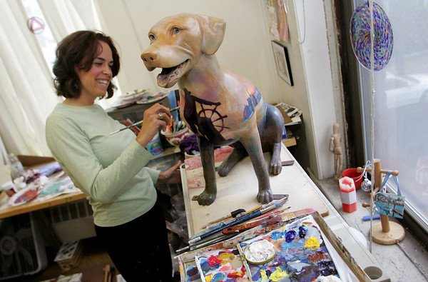 "Gloucester: Loren Doucette works on her dog she titled ""As the Sun Sets on Cape Ann"" in her studion Wednesday evening.  Pathways for Children's ""Pathways Unleashed"" features dogs painted by local artists will be exhibited throughout Cape Ann before being auctioned to the highest bidder at a gala auction. Mary Muckenhoupt/Gloucester Daily Times"
