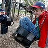 Manchester: Michael Cinelli, 9 months, looks over as Allen Martin, 7, climbs into a baby swing at Masconomo Park yesterday afternoon. The swing was a little too small for Martin, so he got out and helped push Cinelli. Photo by Kate Glass/Gloucester Daily Times Thursday, May 7, 2009