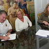 Gloucester: Deputy Fire Chief Stephen Aiello signs an agreement to changes in insurance policies for covering city imployees in the mayor's office Thursday afternoon.  To the right of Aiello is Andrea Pretzler, president of the Gloucester teachers association, and Mayor Carolyn Kirk. Mary Muckenhoupt/Gloucester Daily Times