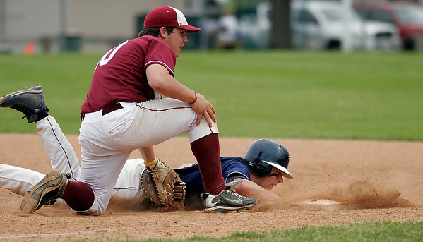 Danvers: Danvers' Kyle Larson is safe diving back to first base as Gloucester's Trevor Curley misses the throw from pitcher Dylan Maki during the consolation game of the Woodman tournament in Danvers yesterday. Photo by Kate Glass/Gloucester Daily Times Sunday, May 24, 2009