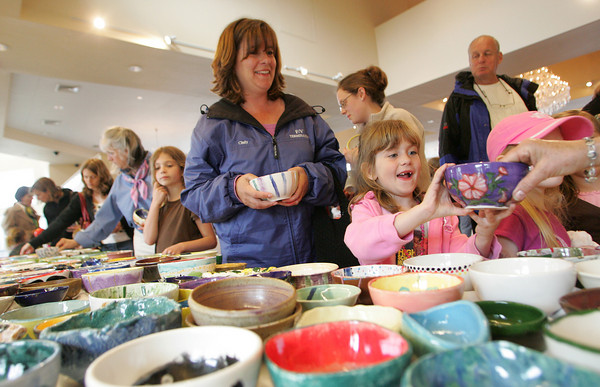 Gloucester: Olivia Theriault, 7, of Rockport chooses a purple bowl with pink flowers, two of her favorite colors, while picking out a bowl with her mom, Cindy, at the Open Door/Cape Ann Food Pantry's nineth annual Empty Bowl Dinner held at Cruiseport Thursday evening.  Cinduy chose a lovely striped bowl that her daughter Olivia had painted with her Daisy troop. Mary Muckenhoupt/Gloucester Daily Times