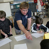 "Rockport: Illustrator Timothy Basil Ering talks to forth anf fifth grade students about their drawings in Simon Paddock's art room Friday morning.  Ering was visiting as part of the artist in residency program and talked to kids about his art work that lead up to him illustrating ""The Tale of Despereaux."" The forth and fifth graders created thir own books with the help of Ering and their classroom teachers. Pictured, from left, Ethan Andersen, Luke Fariel, Ering, Jack Rukeyser and Sophia Graham. Mary Muckenhoupt/Gloucester Daily Times"
