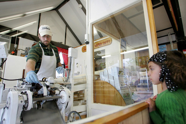 Rockport: Andrew Marques runs vanilla taffe through a machine that individually wraps each piece of candy as Rose Tinkjian, 4, looks on at Tuck's Candy in Dock Square Thursday afternoon. Mary Muckenhoupt/Gloucester Daily Times