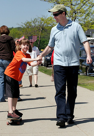 Gloucester: Alix Livermore, 7, holds on to her father, John Livermore, as they make their way down the Boulevard following yesterday's Memorial Day ceremony at Kent Circle. Photo by Kate Glass/Gloucester Daily Times Monday, May 25, 2009