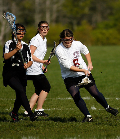 Gloucester: Gloucester's Jennaule Orrell scoops up a ground ball as teammate Brianna Aloisio, center, and Cambridge's Gina Chen, left, look on at Magnolia Woods yesterday. Photo by Kate Glass/Gloucester Daily Times Monday, May 18, 2009