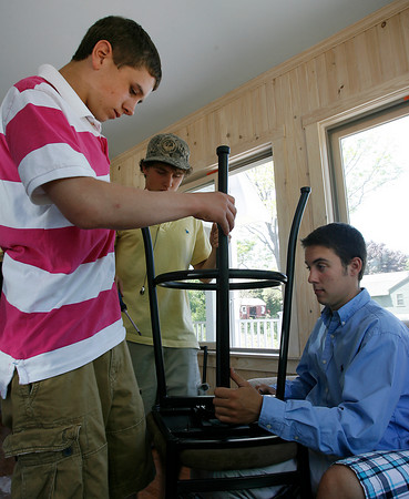 Gloucester: Gloucester High students Brandon Peavey, left, Chris Paul, center, and Nick DeCoste, right, assemble a bar stool during an open house at a home in Lanesville that students in the GHS vocational programs have built. Students have been working on the home for four years and it will be ready for occupants this summer. Photo by Kate Glass/Gloucester Daily Times Friday, May 21, 2009