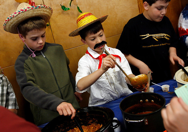 "Essex: Sam Bell and Preston Lee, both fifth grade students at Essex Elementary School, serve chili from a chili contest during the school's Cinco de Mayo event on Tuesday night, which was a fundraiser for the fifth grade class trip. Preston said he grew his mustache overnight, but Sam disagreed, saying ""He grew it a couple hours ago because he didn't have it in school."" Photo by Kate Glass/Gloucester Daily Times Tuesday, May 5, 2009"