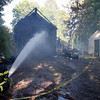 Manchester: Essex firefighter Dan Ball assists Manchester firefighters as they extinguish a three-alarm garage fire on Proctor Street yesterday afternoon. No one was injured in the blaze, though the area was blocked off due to heavy smoke. Photo by Kate Glass/Gloucester Daily Times Thursday, May 21, 2009