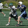Manchester: Manchester Essex's Cody Gillis tries to run past a Triton defender Tom Buswell during the lacrosse game at Ed Field Field Wednesday afternoon.  Triton defeated Manchester Essex 12-3. Mary Muckenhoupt/Gloucester Daily Times