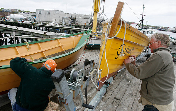Gloucester: Cliff McCarthy, right, and Don Sawyer, left, repaint dory boats behind the Maritime Heritage Center on Wednesday afternoon. The two volunteer their time and say the boats need to be repainted every year. Photo by Kate Glass/Gloucester Daily Times Wednesday, May 6, 2009