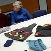 Gloucester: Marge Brennan, left, and Joan Gilson, right, chat while looking at Rose Ann Hunter's projects that use recycled yarns and fabrics during Know Your Knitting (K)Neighbor at the Sawyer Free Library on Monday night. Photo by Kate Glass/Gloucester Daily Times Tuesday, May 12, 2009